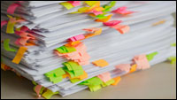 A stack of sheets of printed paper, in which different places in the text are marked with many sticky labels of different colours.