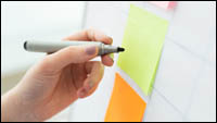 A set of sticky notes on a flipchart, with a hand holding a pen about to write something on one of them.